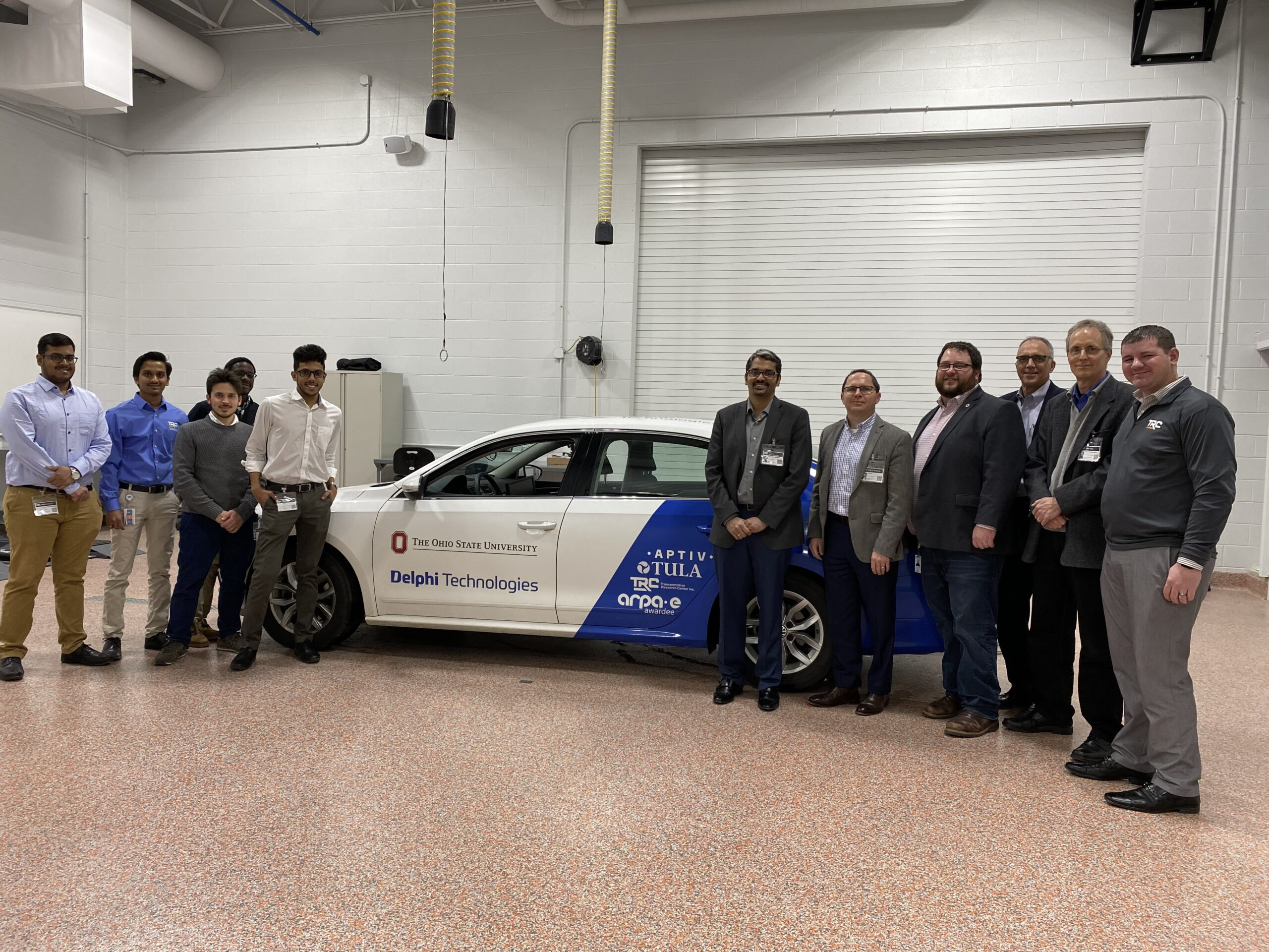 A group of Ohio State students and a group of ARPA-E representatives pose for a group photo with the Ohio NEXTCAR team's vehicle.